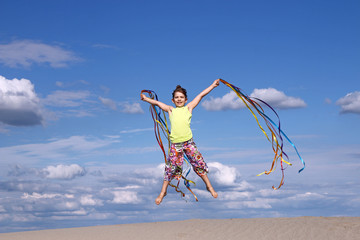 happy little girl jumping on beach