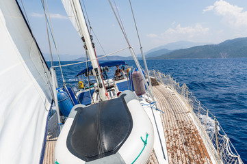 Sailing cruising yacht with women on the helm