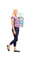 Profile shot of a woman carrying a recycle bin