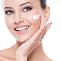 Smiling woman with cosmetic  cream on a clean fresh face
