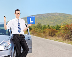 Male driver holding l sign on an open road