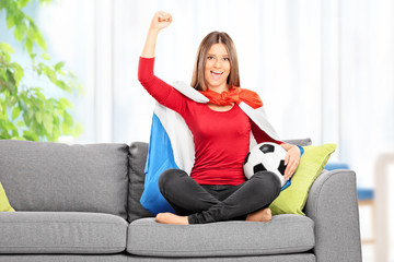 Female football fan cheering seated on sofa at home