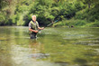 Mature fisherman fishing in a river