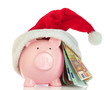 Piggy bank with Santa Claus hat and money on white background