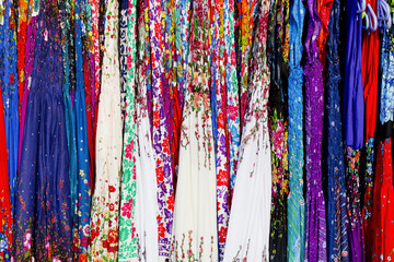 Rows of colourful silk scarfs hanging at a market stall in Thail
