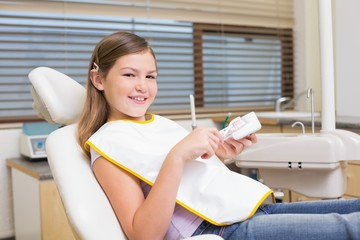 Little girl sitting in dentists chair looking at model teeth