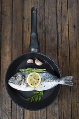 Pescado fresco en la sartén dorada para alimentación saludable