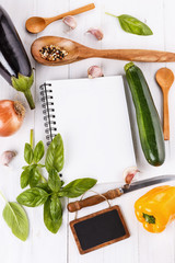 Cooking concept. Recipe book and ingredients for cooking vegetab