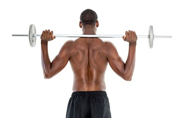 Rear view of a fit shirtless man lifting barbell