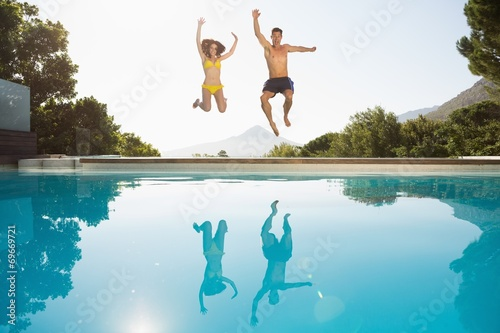 Cheerful couple jumping into swimming pool - 69669721