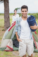 Happy couple with tent on countryside landscape