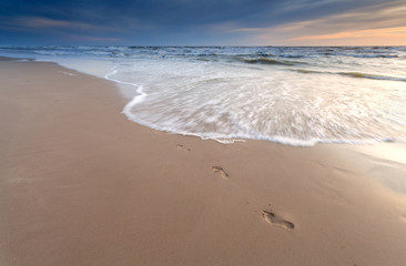 foot prints on sand beach at sunset