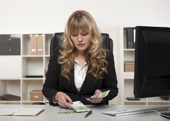 Businesswoman counting out money at her desk