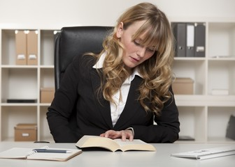 Young businesswoman reading a book at work