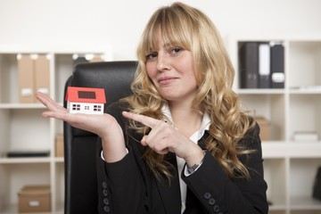 Corporate Woman Pointing Model House on Palm