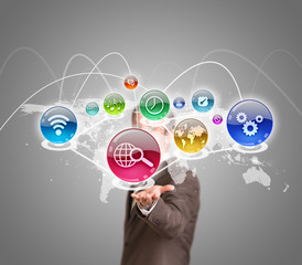 Businessman in suit holding world map with app icons