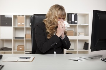 Businesswoman blowing her nose at her desk