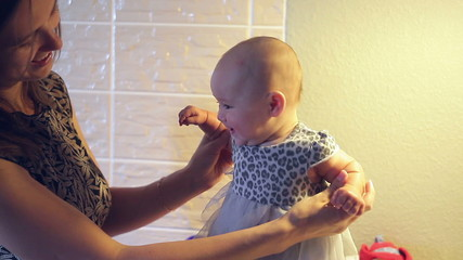 Mom keeps a little baby girl in a dress in her hands