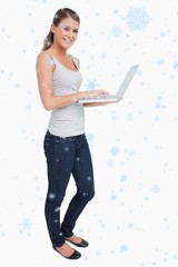 Composite image of portrait of a smiling woman using a laptop