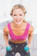 Fit blonde lifting dumbbells and smiling at camera