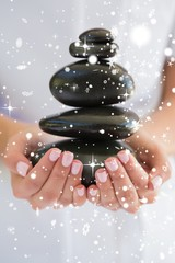 Therapist holding pile of stones for massage