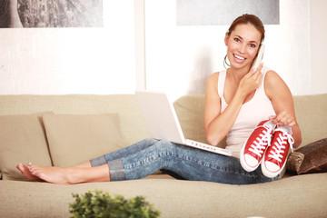 Frau beim telefonieren und zeigt rote Schuhe