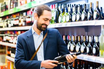 Mann wählt Wein im Supermarkt