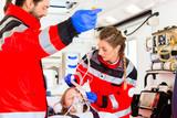 Notärzte helfen verletzte Frau in Ambulanz - 69679118