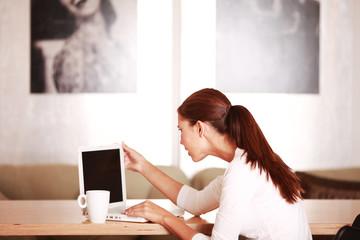 junge Frau konzentriert am Laptop