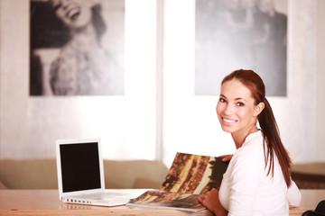 junge Frau mit Magazin und Laptop