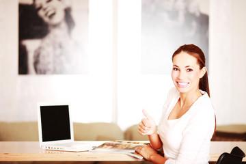 junge Frau mit Zeitschrift und Laptop