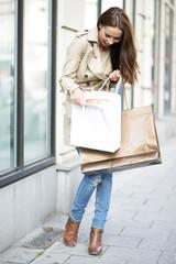 Frau schaut in Einkaufstaschen