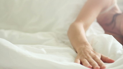 Woman smoothing a fresh white bedding