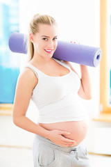 Pregnant woman holding yoga mat