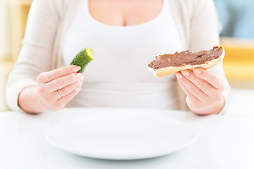 Pregnant woman with pickle and chocolate sandwich