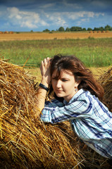 Yoing woman in haystacks on fields