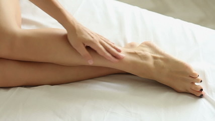 Legs of a woman with a white sheet on a bed, slow motion