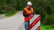 Worker with wrench repairing road sign
