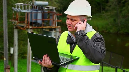 Engineer working with PC near High voltage power transformer