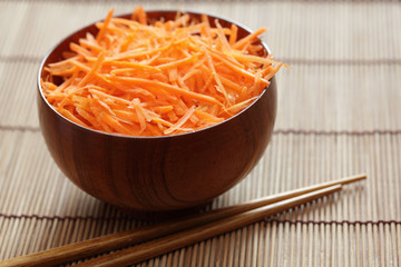Grated carrots in bowl with chopsticks