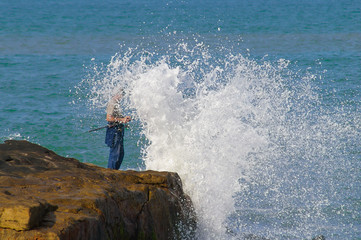 Fisherman is surprised by a wave