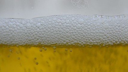 A pint glass is slowly filled with refreshing beer