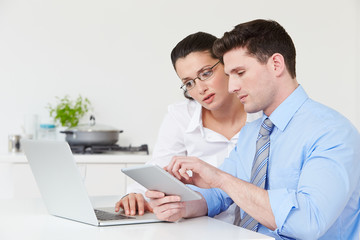 Couple Using Laptop And Digital Tablet At Home
