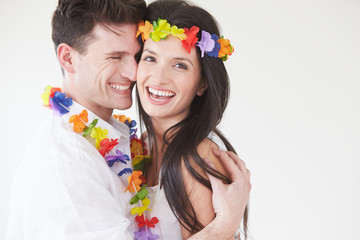 Couple Wearing Flower Garlands Against White Background