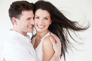 Romantic Couple Embracing Against White Studio Background