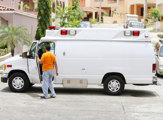 White ambulance with the driver getting out to help the paramedi