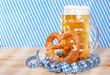 canvas print picture -  Eine Mass Bier mit Brezel vor weißblauen Luftschlangen