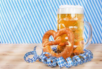 Eine Mass Bier mit Brezel vor weißblauen Luftschlangen