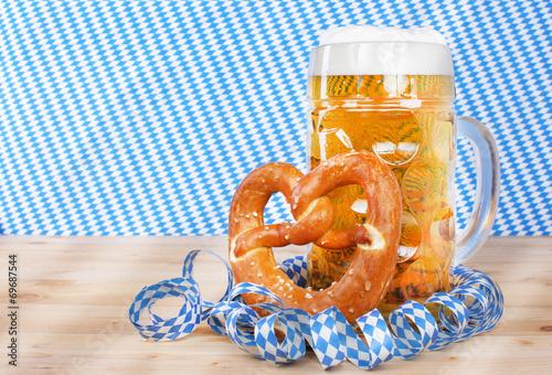 canvas print picture  Eine Mass Bier mit Brezel vor weißblauen Luftschlangen