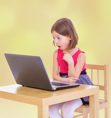 Surprised little girl looking into the computer.
